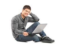 Un maschio sorridente con un computer portatile che esamina macchina fotografica Immagine Stock Libera da Diritti