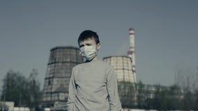 Un masque de port de pollution de garçon contre la fumée émettant des cheminées d'usine Concept de pollution atmosph?rique banque de vidéos