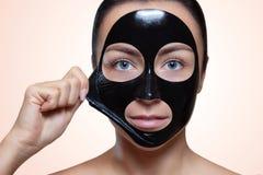 Un masque noir au visage d'une belle femme image stock
