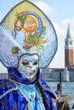 Un Masquerader par un canal à Venise Photographie stock libre de droits