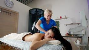 Un massaggiatore professionista che massaggia cliente beautful s indietro con attenzione ad una luce Massaggio di distensione archivi video