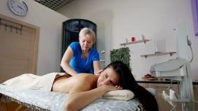 Un massaggiatore professionista che massaggia cliente beautful s indietro e le spalle con attenzione ad una luce Massaggio di dis stock footage