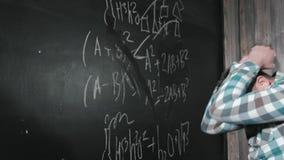 Un mathématicien mûr brillant amène un grand conseil et accomplit une équation compliquée par essai de formule mathématique banque de vidéos