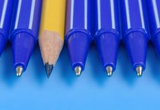 Un matita e gruppo gialli di penne blu Concetto di individualità Fotografia Stock Libera da Diritti