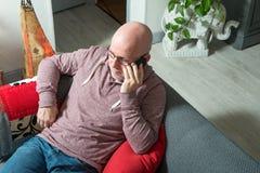 Un mayor con un teléfono que se sienta en el sofá Foto de archivo libre de regalías