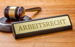 Un mazo y una placa de identificación con el Arbeitsrecht de grabado alemán foto de archivo