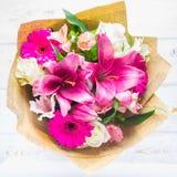 Un mazzo dei fiori da un giglio, da una gerbera, dalle rose bianche e da un alstroemeria su una tavola di legno bianca Una festa, Fotografie Stock Libere da Diritti