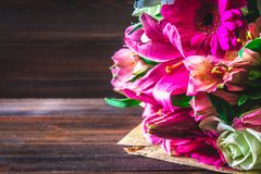 Un mazzo dei fiori dal giglio, dalla gerbera, dalle rose bianche e dal alstroemeria su una tavola di legno marrone Una festa, un  Fotografia Stock