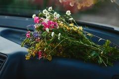 Un mazzo dei fiori selvaggi si trova nell'automobile fotografia stock libera da diritti