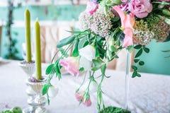 Un mazzo dei fiori su un supporto con le candele e sulla decorazione per la decorazione della tavola alle nozze ed alle celebrazi Immagini Stock