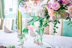 Un mazzo dei fiori su un supporto con le candele e sulla decorazione per la decorazione della tavola alle nozze ed alle celebrazi Fotografia Stock