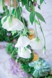 Un mazzo dei fiori su un supporto con le candele e sulla decorazione per la decorazione della tavola alle nozze ed alle celebrazi Fotografia Stock Libera da Diritti
