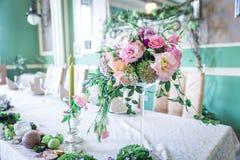 Un mazzo dei fiori su un supporto con le candele e sulla decorazione per la decorazione della tavola alle nozze ed alle celebrazi Fotografie Stock Libere da Diritti
