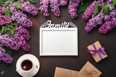 Un mazzo dei lillà con la tazza di tè, una struttura bianca per l'iscrizione, contenitore di regalo, busta del mestiere, una nota fotografia stock