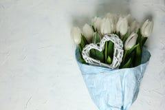 Un mazzo dei tulipani bianchi in carta da imballaggio blu con cuore su un fondo concreto bianco Vista superiore Disposizione pian Fotografia Stock