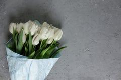 Un mazzo dei tulipani bianchi in carta da imballaggio blu su un fondo concreto grigio Vista superiore Disposizione piana Cartolin Immagine Stock Libera da Diritti