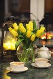 Un mazzo dei tulipani gialli in un vaso all'interno di un retro Immagini Stock Libere da Diritti