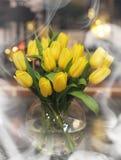 Un mazzo dei tulipani gialli in un vaso all'interno di un retro Immagine Stock