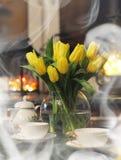 Un mazzo dei tulipani gialli in un vaso all'interno di un retro Immagini Stock