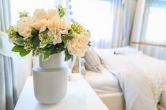Un mazzo del fiore artificiale in un vaso con il letto ed i ciechi indietro fotografie stock libere da diritti