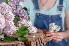 Un mazzo del lillà su un bello taglio di legno e una figura in un denim complessivo nei precedenti fotografie stock libere da diritti