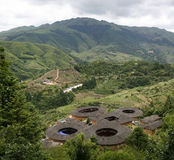 Un mazzo della hakka Tulou si dirige la trascuratezza la valle e della catena montuosa in Yongding Cina Fotografia Stock