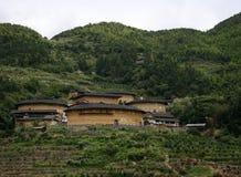 Un mazzo della hakka Tulou si dirige nella valle di appoggio dalla catena montuosa Fotografia Stock