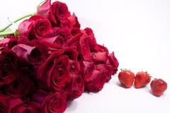 Un mazzo delle rose rosse e delle fragole immagini stock