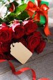 Un mazzo delle rose rosse su una tavola immagine stock