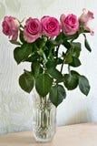 Un mazzo delle rose in un vaso sulla tavola immagine stock