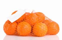 Un mazzo di arance imballate in reticolato rosso, isolato su bianco immagini stock libere da diritti