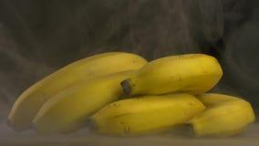 Un mazzo di banane fresche su un fondo nero da cui viene sudato e fresco, fumo, primo piano, 4K stock footage