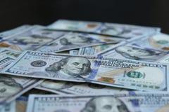 Un mazzo di 100 banconote in dollari su fondo nero Fotografie Stock Libere da Diritti
