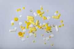 Un mazzo di bianco e di molte piccole pillole gialle Fotografie Stock Libere da Diritti