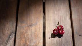 Un mazzo di ciliege su una superficie di legno della tavola Immagine Stock Libera da Diritti