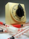 Un mazzo di droghe, siringhe che circondano un cronometro Fotografia Stock