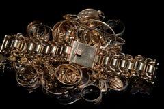 Un mazzo di gioielli differenti dell'oro su un fondo nero fotografie stock libere da diritti