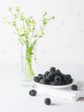 Un mazzo di more su un piatto bianco Fondo e mazzo leggeri dei fiori Un'alta chiave Fotografie Stock