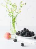 Un mazzo di more su un piatto bianco Fondo e mazzo leggeri dei fiori Un'alta chiave Fotografia Stock