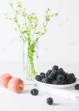Un mazzo di more su un piatto bianco Fondo e mazzo leggeri dei fiori Un'alta chiave Immagini Stock Libere da Diritti