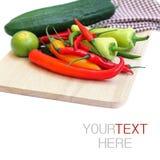 Un mazzo di peperoncini rossi, di calce e di cetriolo sul tagliere Immagini Stock