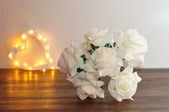 Un mazzo di rose artificiali bianche con da forma del cuore della luce del fuoco Immagini Stock Libere da Diritti