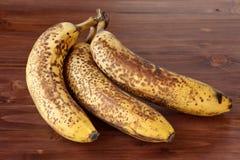 Un mazzo di tre marci, banane macchiate su una superficie di legno marrone Immagini Stock