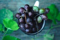 Un mazzo di uva in una tazza bianca su un fondo verde di legno fotografie stock libere da diritti