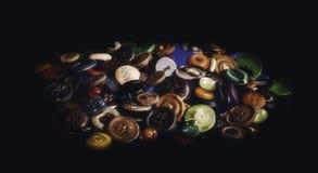 Un mazzo di vecchi bottoni su fondo nero fotografie stock libere da diritti