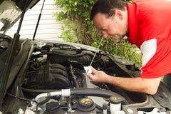 Un mécanicien Checking The Oil dans une plus nouvelle voiture Image libre de droits