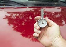 Un mecánico Checking Tire Pressure con un indicador del neumático Foto de archivo libre de regalías