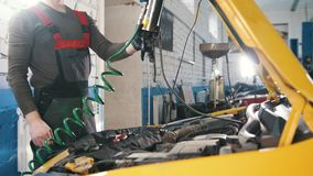 Un mecánico comprueba el eléctrico en la capilla de la reparación automotriz en el compartimiento del reactor almacen de metraje de vídeo