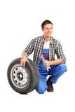 Un mecánico de sexo masculino que presenta con un neumático de repuesto foto de archivo libre de regalías