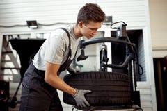 Un mecánico hermoso está ayudando a sus compañeros de trabajo en un servicio del coche fotos de archivo